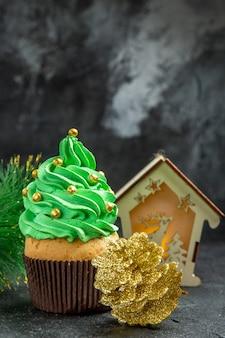 Vista dall'alto mini albero di natale cupcake rami di albero di natale lanterna pigna dorata su sfondo scuro posto libero
