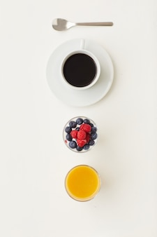 Top view at minimal composition of delicious dessert decorated with fresh berries next to coffee cup, breakfast concept