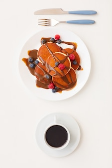 Top view at minimal composition of delicious golden pancakes decorated with chocolate and fresh berries next to coffee cup, breakfast and dessert concept
