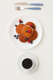 Top view at minimal composition of delicious golden pancakes decorated with fresh berries next to coffee cup, breakfast concept