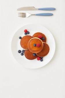 Top view at minimal composition of delicious golden pancakes decorated with fresh berries next to knife and fork, breakfast concept