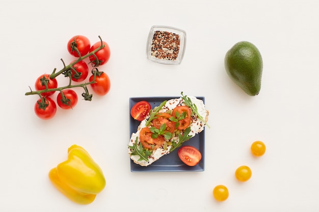 Top view at minimal composition of fitness bruschetta with cherry tomatoes and herbs decorated by healthy breakfast ingredients