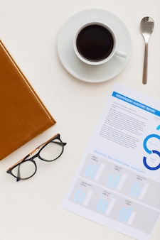 Top view at minimal composition of single coffee cup next to business items and black-rimmed glasses