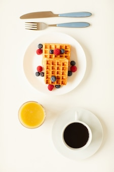 Top view at minimal composition of sweet dessert waffles with berry topping next to cup of black coffee