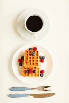 Top view at minimal composition of sweet dessert waffles with berry topping next to single cup of black coffee