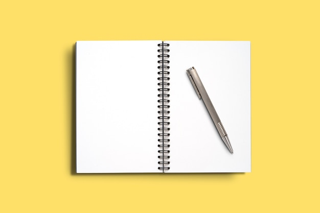 Top view minimal design of open notebook with pen on yellow background.