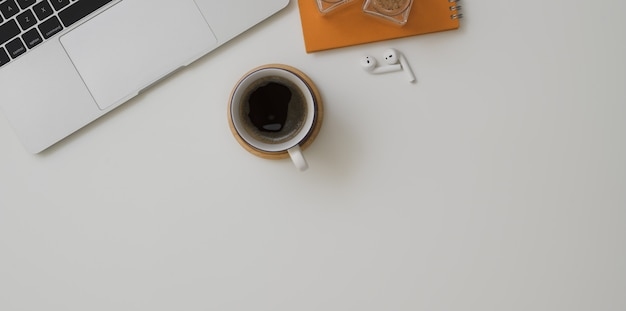 Top view of minimal workspace with laptop computer, a cup of coffee and office supplies
