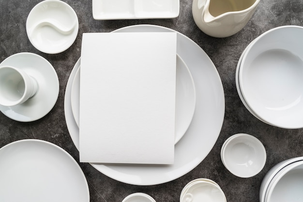 Top view of minimalist white plates with empty menu