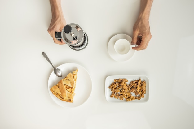 Top view of minimalistic table with business lunch with coffee, cereal and apple pie.
