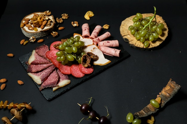 Top view misnaya plate with grapes and nuts on a stand with dried fruits on a black table