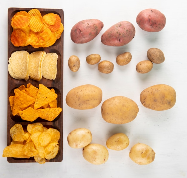 Top view mix chips corn chips paprika potato chips nachos chips and raw potato on white background