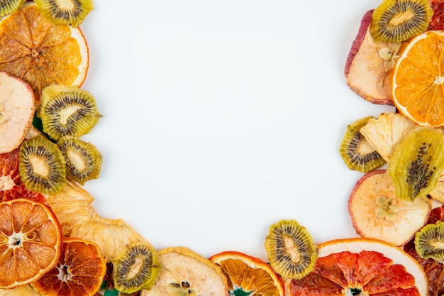 Top view of mix of dried fruits and citruses apple orange kiwi and pineapple slices on white background with copy space