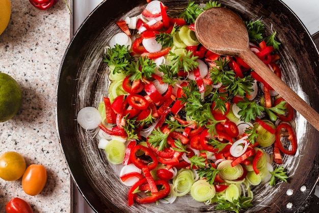Top view of the mix of fresh vegetables in the rustic pan with a wooden spoon