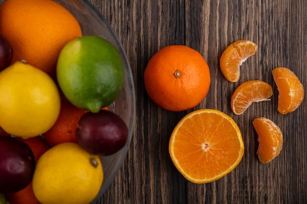 Vista dall'alto mix di frutta limoni limette prugne pesche e arance in un vaso su uno sfondo di legno