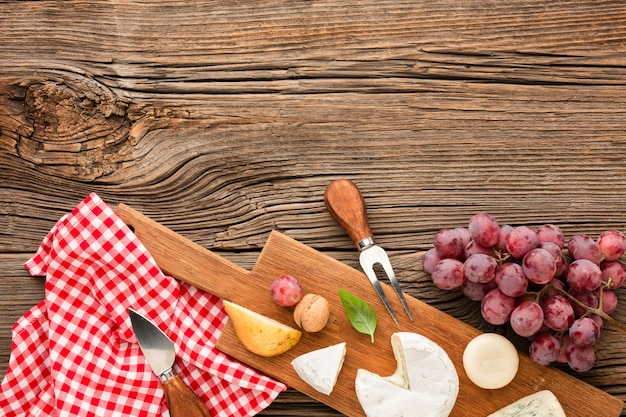 Top view mix of gourmet cheese on wooden cutting board with grapes