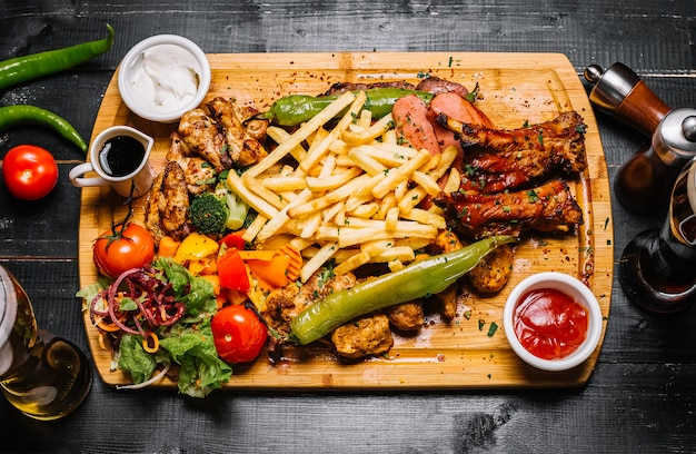Top view mix of meat snacks with french fries grilled vegetables salad and sauces on the board