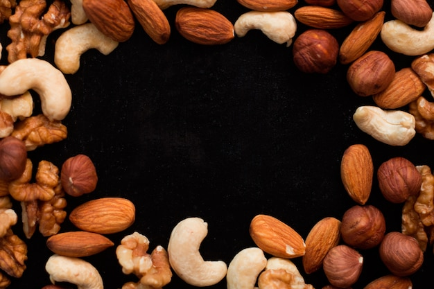 Top view mix of nuts frame on a black table
