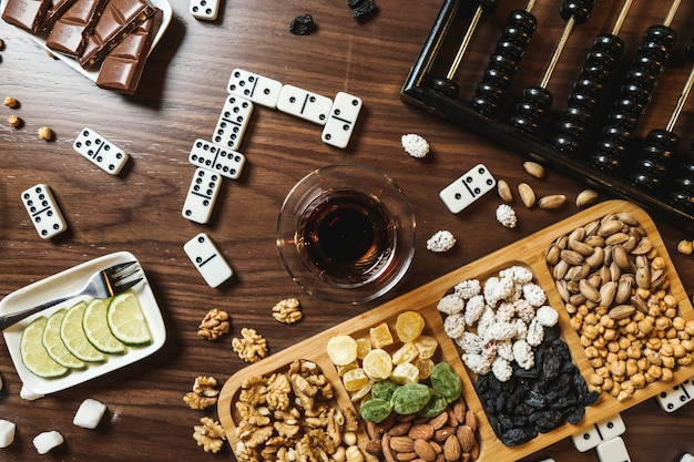 Top view mix of nuts with tea lemon slices chocolate bar dominoes and abacus on the table