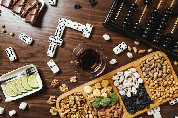 テーブルの上の茶レモンスライスチョコレートバードミノとそろばんとナッツのトップビューミックス