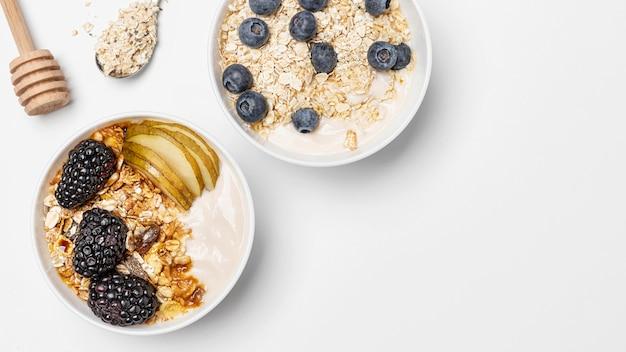 Вид сверху микс йогурта с овсом и фруктами в мисках с копией пространства