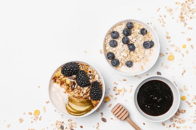 Вид сверху смесь йогурта с овсом, фруктами и медом