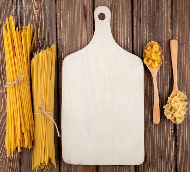 Bucatini di farfalle di maccheroni del gomito della pasta della vista superiore e pasta degli spaghetti su fondo di legno