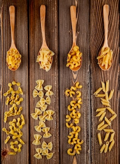 Top view mix pasta farfalle elbow macaroni penne and farfalle tonde pasta on wooden background