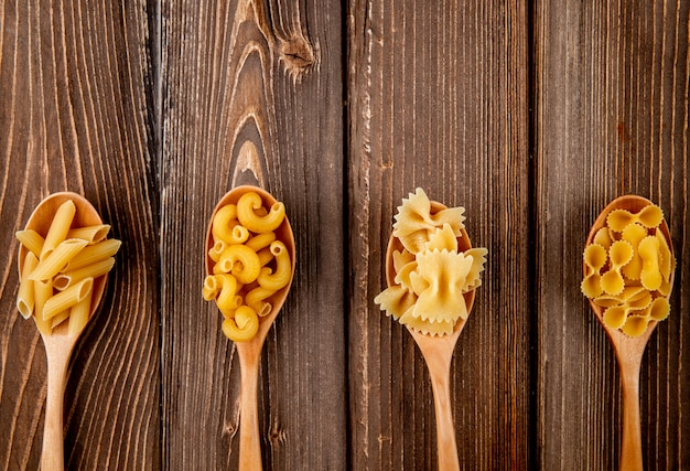 Top view mix pasta farfalle penne elbow macaroni and farfalle tonde with copy space on wooden backgound