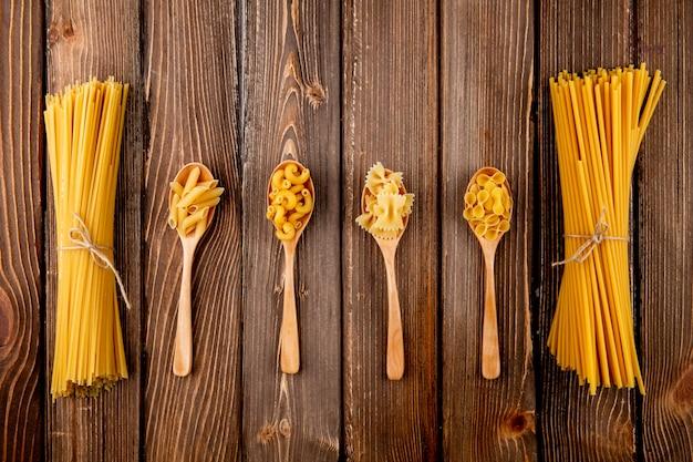 Vista dall'alto mescolare pasta spaghetti bucatini farfalle penne gomito maccheroni e farfalle tonde su fondo di legno