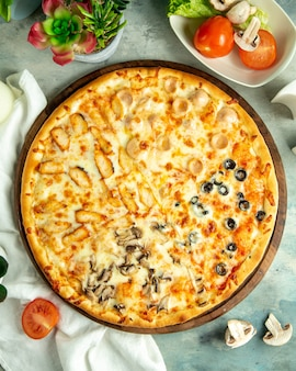 Top view mix pizza with chicken sausages mushrooms and olives on the board