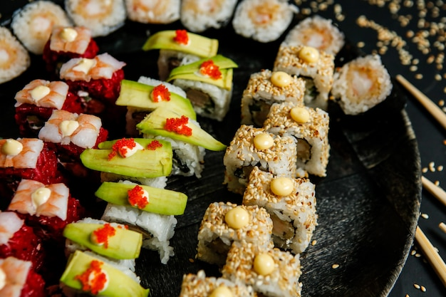 Top view mix rolls with avocado sesame seeds and chopsticks on a stand