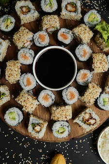 Top view mix rolls with soy sauce on a stand with sesame seeds