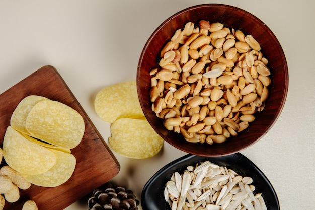 Top view of mix of salty snacks to beer  peanuts in a wood bowl potato chips and sunflower seeds on white