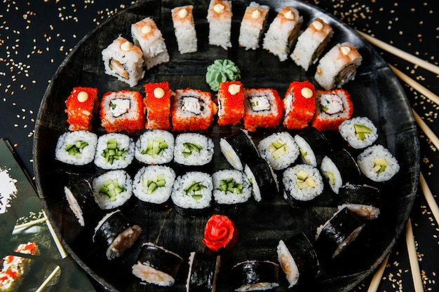 Top view mix sushi rolls on a plate with wasabi and ginger