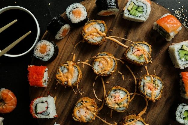 Vista dall'alto mescolare rotoli di sushi su un supporto con salsa di soia allo zenzero wasabi semi di sesamo e avocado