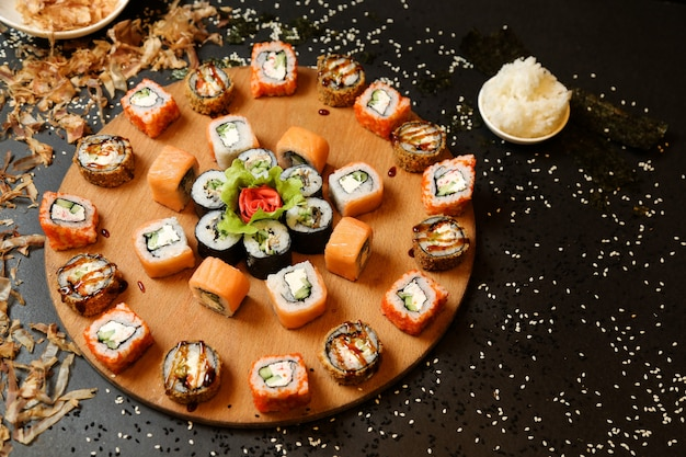 Top view mix of sushi and rolls with wasabi and ginger on a stand