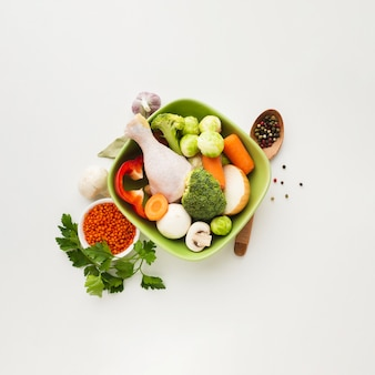 Top view mix of vegetables in bowl with chicken drumstick