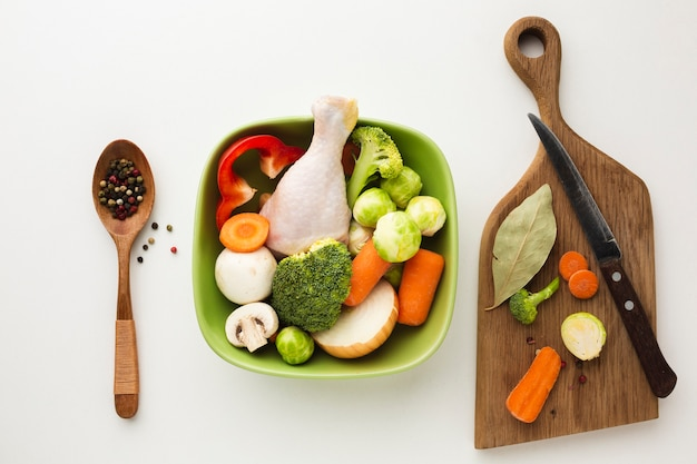 Top view mix of vegetables on cutting board and in bowl with chicken drumstick and spoon