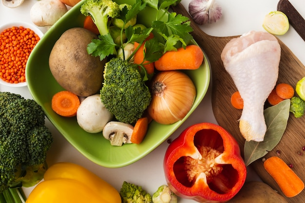 Top view mix of vegetables on cutting board and in bowl with chicken drumstick