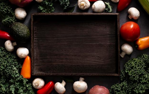 Vista dall'alto mix di verdure con vassoio in legno vuoto