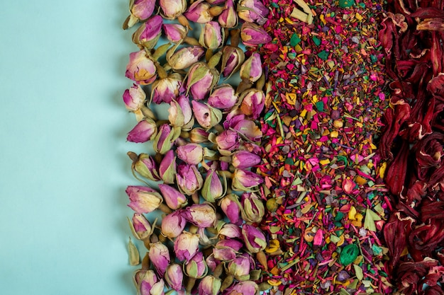 Top view of mixed herbal tea blooms rose petals dried rose buds and herbs on blue