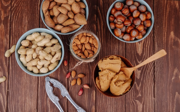 Top view of mixed nuts and a bowl with peanut butter with a nut cracker on wooden background
