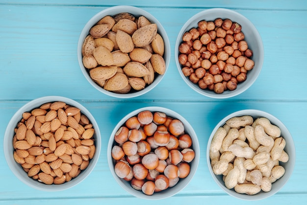 Top view of mixed nuts in shell and without shell in bowls almond hazelnuts and peanuts on blue background