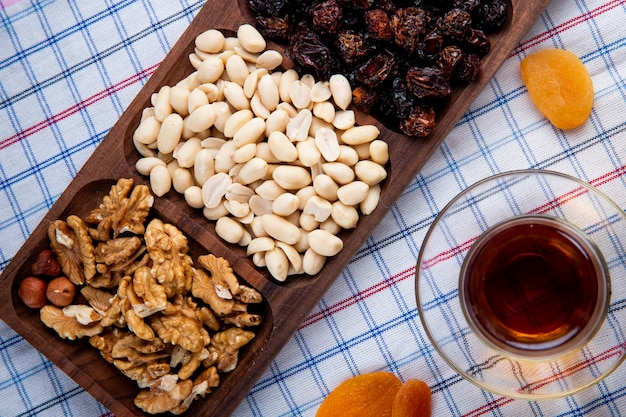 Top view of mixed nuts with dried fruits in a wood box served with tea in armudu glass on the tablecloth