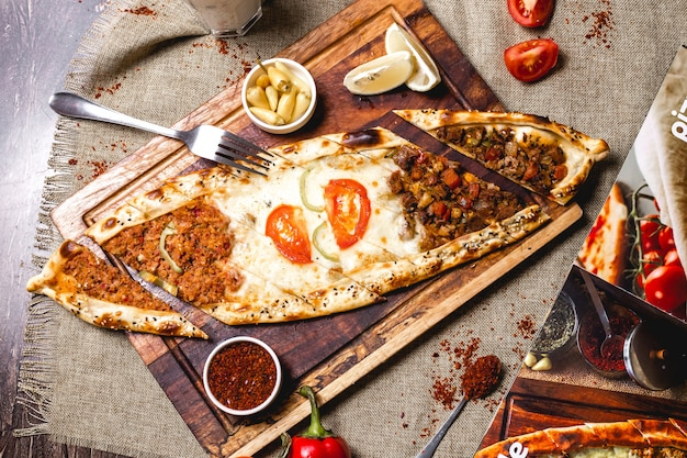 Top view of mixed pide with minced meat ground beef and cheese