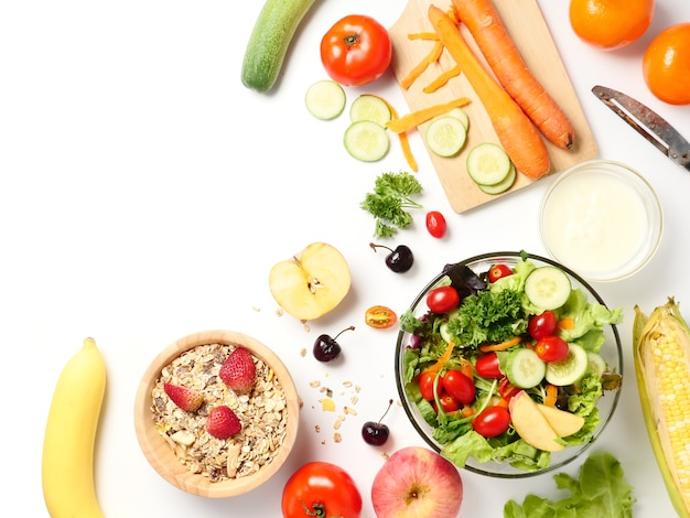 Top view of mixed vegetables salad, muesli and fresh fruits on white background