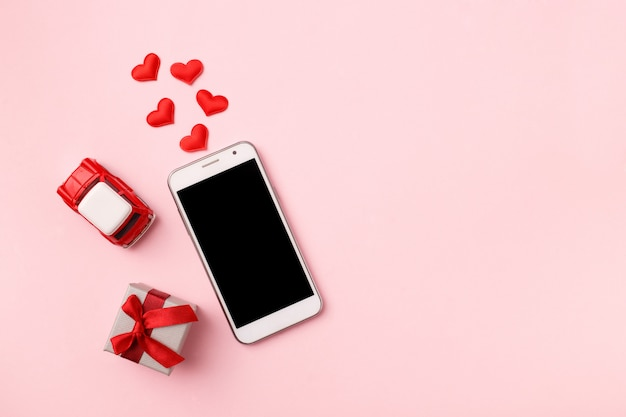 Top view of mobile cellphone and red heart confetti, toy car on pink pastel , copyspace. mockup template for valentines day. love, technology . top view, flat lay.