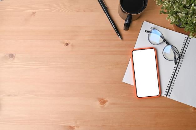 平面図の携帯電話、ノートブック、メガネ、コーヒーカップ、木製の背景に観葉植物。