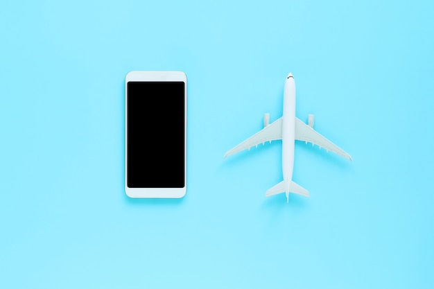 Top view of mobile and plane on blue isolated background with copy space