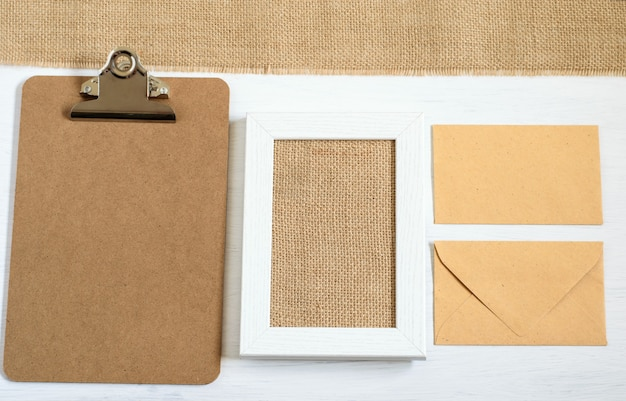 Top view on mock up photo with clip board, picture frame, envelopes and burlap cloth on the white background.